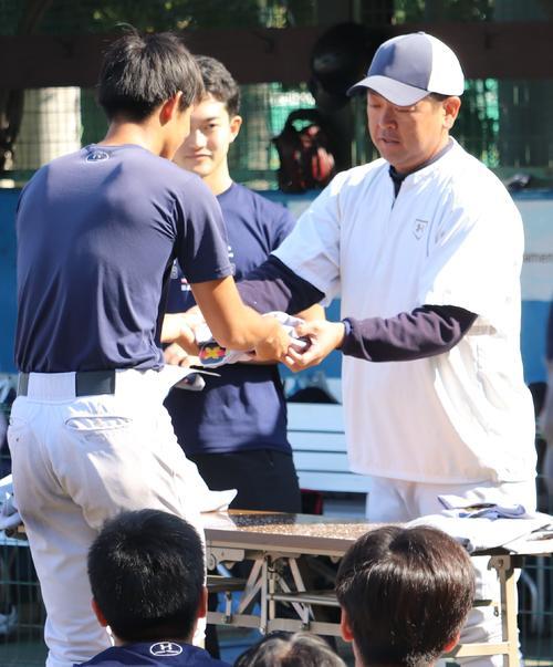 早慶戦を翌日に控えた練習後、慶大・大久保監督(右)はメンバーにユニホームを手渡す(撮影・古川真弥)