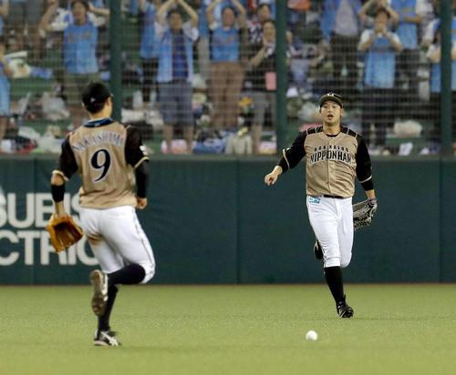 7月28日、西武戦の10回裏1死一塁で秋山の打球を後逸する日本ハム中島(左)