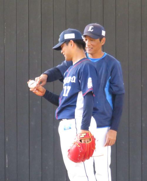ブルペンで西武松本航(左)にスライダーの握りを伝授する西口投手コーチ(19年11月7日)