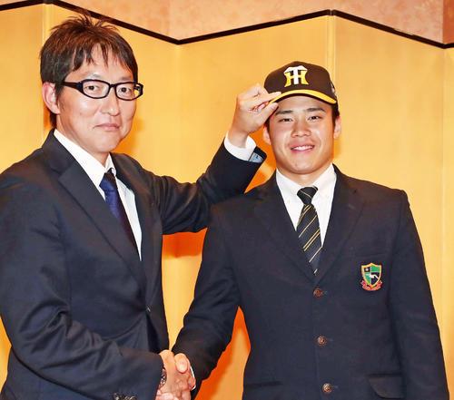 仮契約を終えて吉野スカウト(左)と写真に納まる阪神のドラフト4位・遠藤(撮影・丹羽敏通)