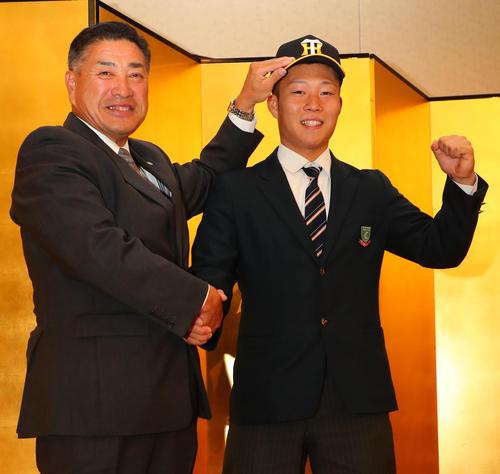 阪神と仮契約を結んだ藤田(右)は熊野担当スカウトに帽子をかぶせてもらい笑顔で握手を交わす(撮影・宮崎幸一)