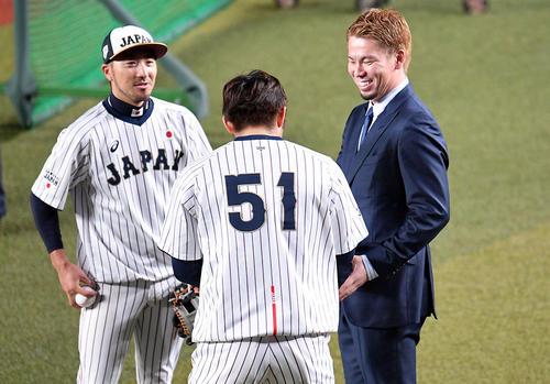 オーストラリア戦の試合前練習で前田(右)と握手を交わす鈴木(手前)。左は菊池涼(撮影・滝沢徹郎)