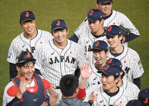 日本対オーストラリア オーストラリアに勝利してベンチで秋山(下)の出迎えを受け、笑顔を見せる鈴木(中央左)、周東(同右)ら侍ジャパンナイン(撮影・加藤諒)