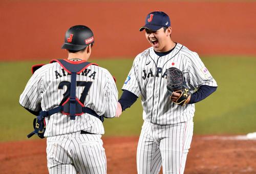 日本対オーストラリア 9回を抑えた山崎(右)は会沢と握手を交わす(撮影・滝沢徹郎)