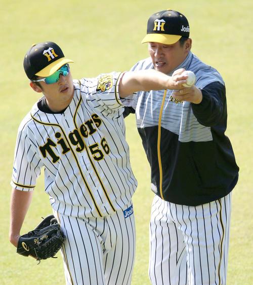 サブグラウンドで飯田(左)を指導する山本昌臨時コーチ(撮影・上山淳一)