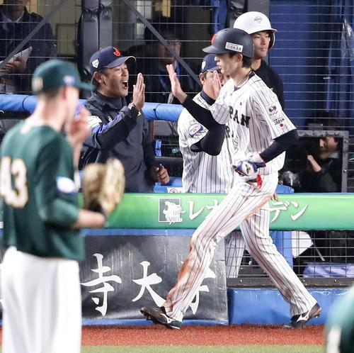 日本対オーストラリア 7回裏日本2死三塁、源田のセーフティーバントで同点の生還をした周東(手前)を笑顔で迎える稲葉監督(奥)(撮影・浅見桂子)