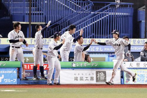 日本対オーストラリア 7回裏日本2死三塁、源田のセーフティーバントで同点の生還をした周東(右)を笑顔で迎える日本ナイン(撮影・浅見桂子)