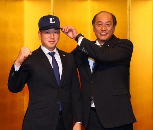 西武との仮契約を終え、渡辺GM(右)に帽子をかぶせてもらう東芝・宮川(撮影・大野祥一)