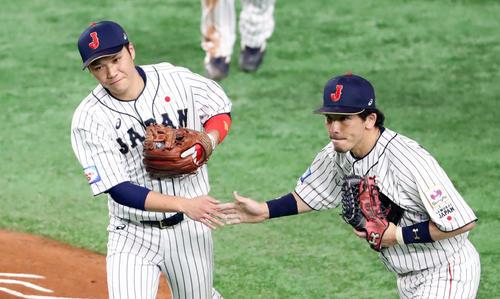 日本対メキシコ 2回表メキシコ2死、ソリスを遊ゴロに仕留めた坂本(左)は松田とタッチを交わす(撮影・垰建太)