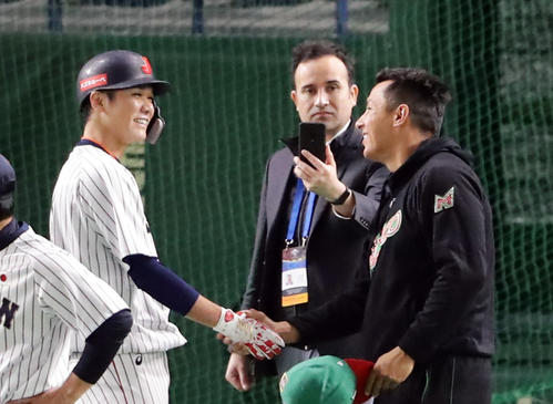 日本対メキシコ 試合前、握手する坂本勇(左)とナバーロ(撮影・浅見桂子)