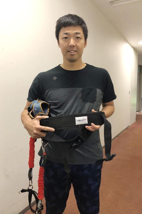 投球の際、右足に装着する練習器具を手に新フォームへの手ごたえを語る中日吉見