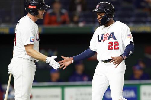 台湾対アメリカ 1回裏アメリカ1死二塁、ボーンの左前適時打で生還し、クラツ(左)に迎えられるアデル(撮影・前田充)