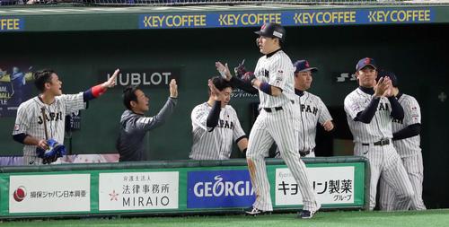日本対韓国 3回裏日本無死一、二塁、浅村の適時打で生還した丸(手前)はナインの出迎えを受ける。右は拍手する稲葉監督(撮影・垰建太)