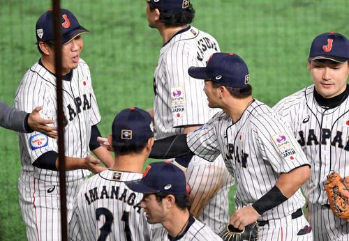 日本対韓国 5回に好返球を見せた鈴木(右から2人目)とタッチを交わす大野雄(左)(撮影・滝沢徹郎)