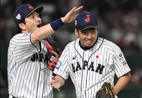 日本対韓国 7回表韓国2死一、二塁、相手を三振に仕留めた嘉弥真(右)は松田宣に頭をなでられる(撮影・山崎安昭)