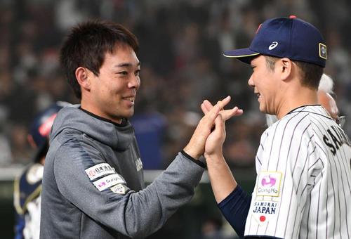 日本対韓国 タッチをかわして勝利を喜ぶ秋山(左)と坂本勇(撮影・山崎安昭)