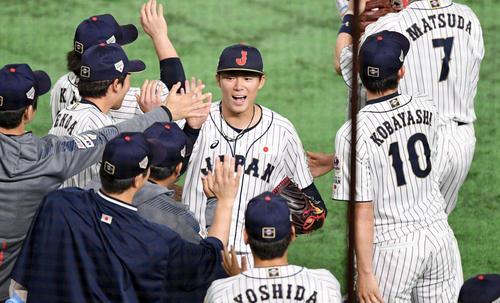 日本対韓国 8回表を投げ終えた山本(中央)は笑顔でナインとタッチを交わす(撮影・滝沢徹郎)