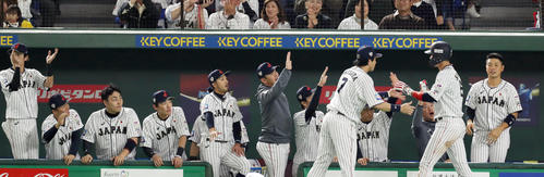日本対韓国 1回裏日本2死一塁、鈴木の適時二塁打で生還した坂本勇(右から2人目)をタッチで迎える日本ナイン(撮影・前田充)
