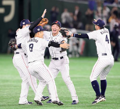 日本対韓国 優勝を決め左から丸、近藤と抱き合う鈴木、右は菊池涼(撮影・加藤哉)