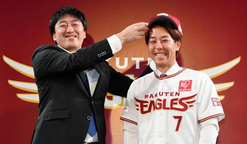 楽天入団会見で石井GM(左)から帽子をかぶせてもらう鈴木(2019年11月27日)