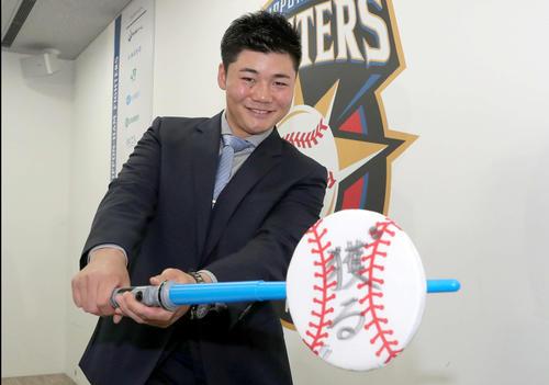 ライトセーバー風の玩具をバットに見立てて来季の抱負を記したボールを打つ日本ハム清宮(2019年11月27日)