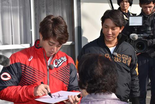 真備町の仮設住宅でサイン会を行う広島野村(左)と巨人小林