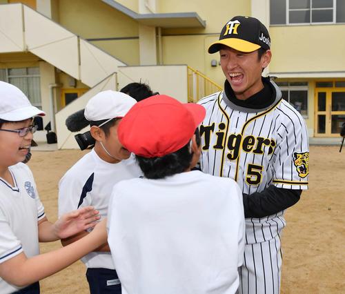 摂陽小学校を訪れ児童と笑顔で握手を交わす近本光司(撮影・上田博志)