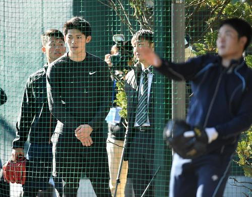 ブルペンで投球練習するロッテ種市の投球を見学する佐々木朗(撮影・横山健太)