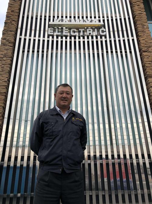現在勤務するカミヤ電機本社前に立つ野口茂樹氏