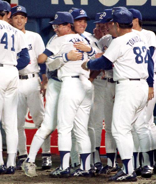 巨人を破り首位に並んだ高木監督は8勝目を挙げた郭と抱き合い笑顔を見せる(1994年撮影)