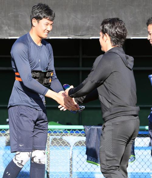 小川泰弘(右)と笑顔で握手を交わすヤクルトドラフト1位の奥川恭伸(撮影・たえ見朱実)