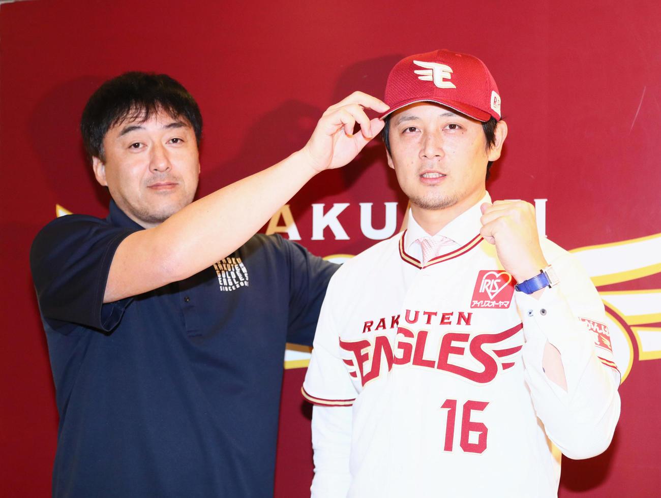 トレードで楽天に加入した涌井秀章(右)は石井一久GMから帽子をかぶせてもらう(19年12月23日撮影)