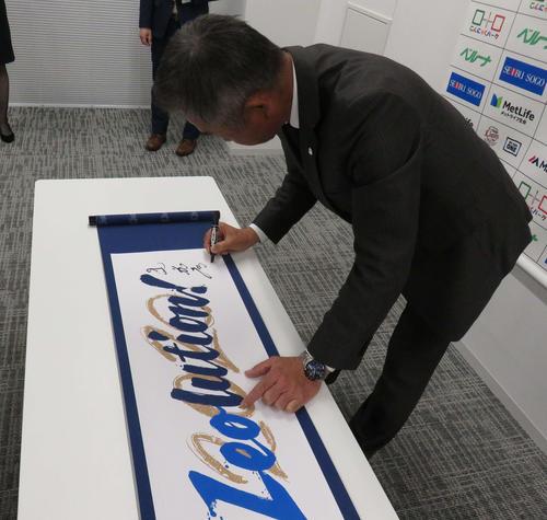 新スローガン「Leolution!」の巻物にサインをする西武辻監督(撮影・栗田成芳)