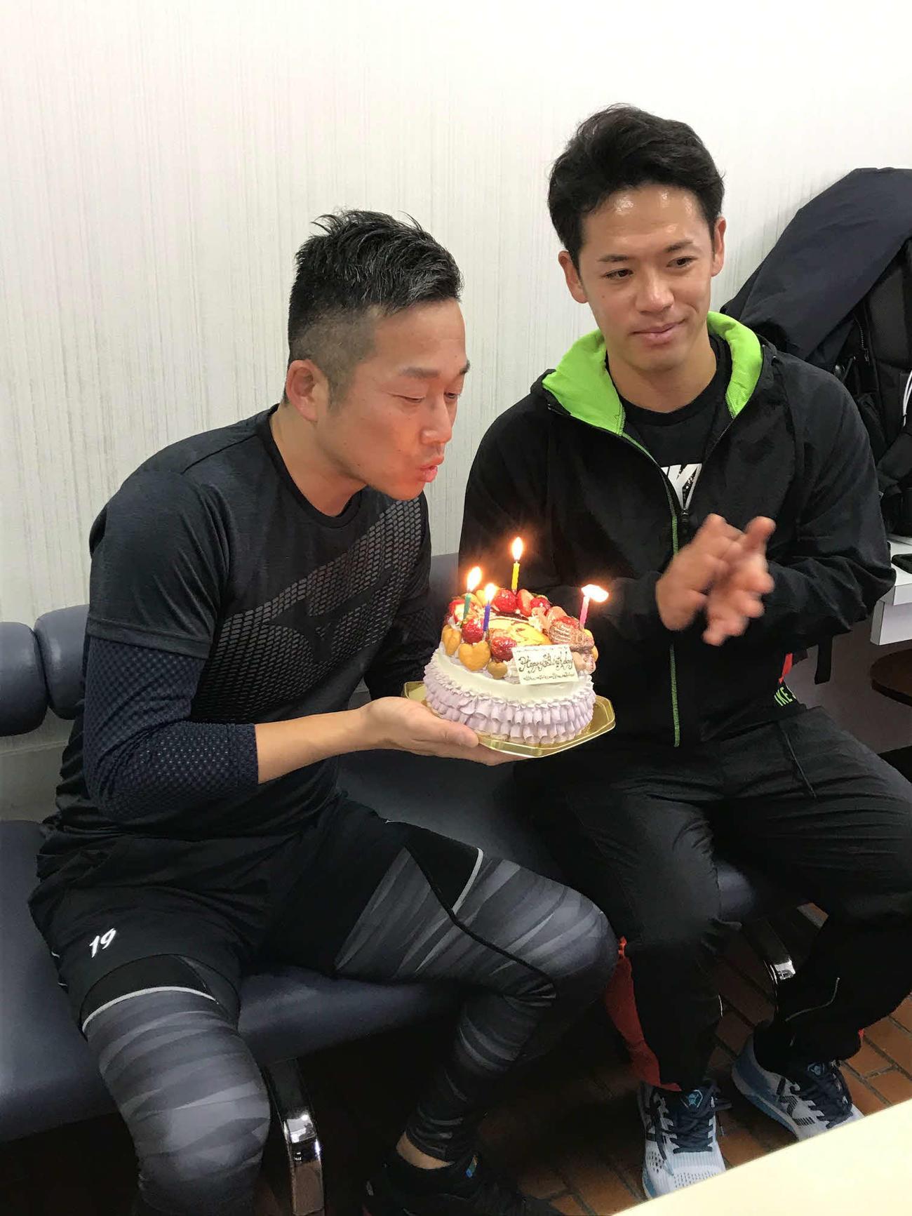 22日に40歳の誕生日を迎えろうそくの火を消すヤクルト石川(左)と祝福する小川(撮影・保坂恭子)