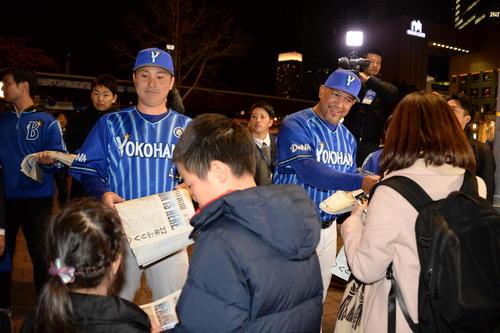 DeNA新主将に就任した佐野はラミレス監督とともにJR桜木町駅前で号外を配る(撮影・鈴木正章)