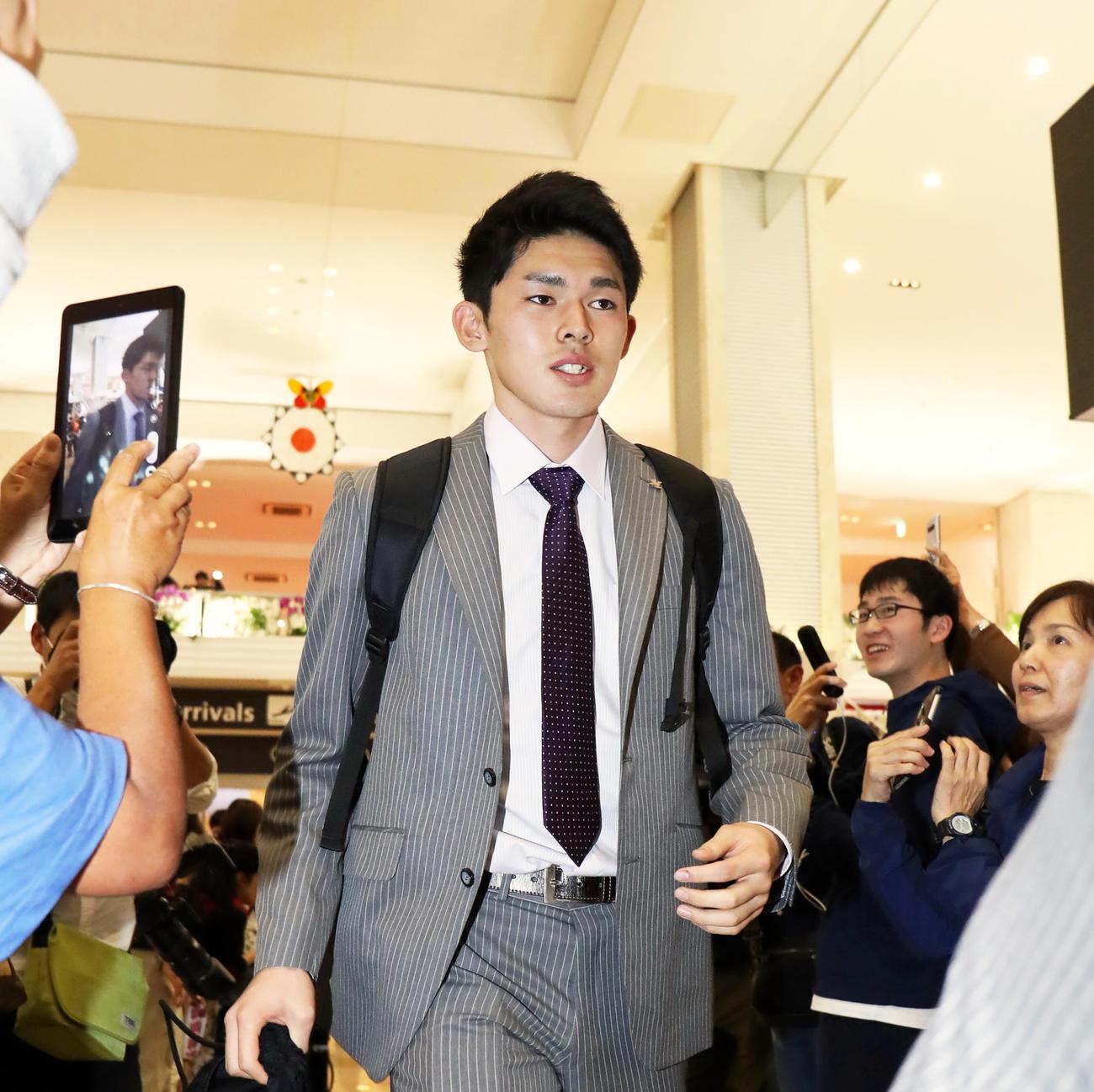 居合わせた観光客と報道陣の視線を浴びながら新石垣空港に到着したロッテ佐々木朗希(撮影・垰建太)