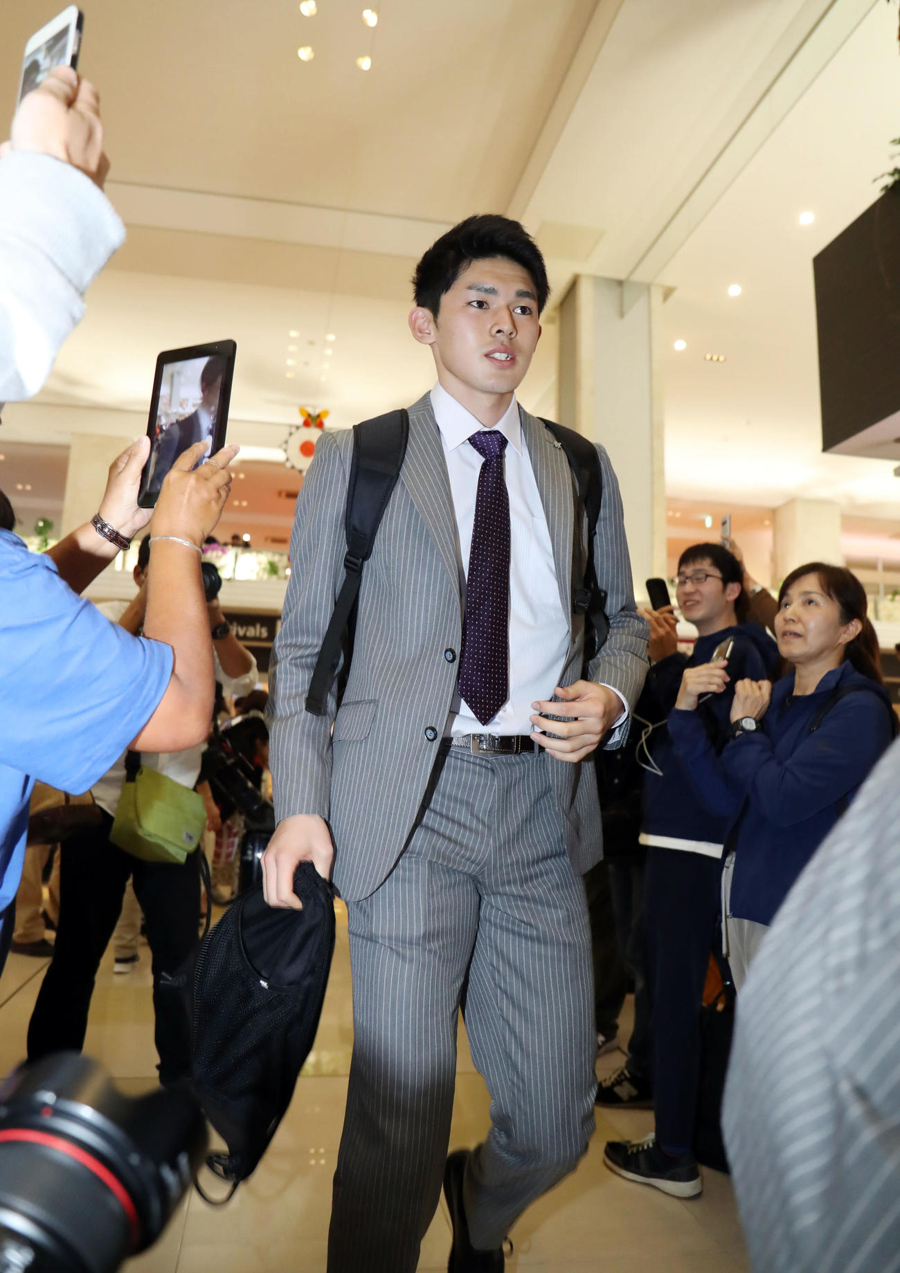 居合わせた観光客と報道陣の視線を浴びながら新石垣空港に到着したロッテ佐々木朗(撮影・垰建太)