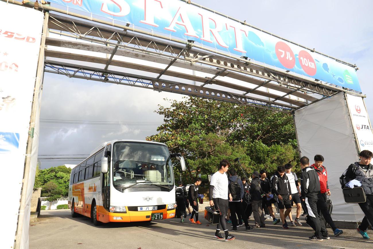 バスが前日行われたマラソンのスタートゲートにぶつかりくぐれず停車した場所から歩いて球場に向かうロッテの選手たち(撮影・垰建太)