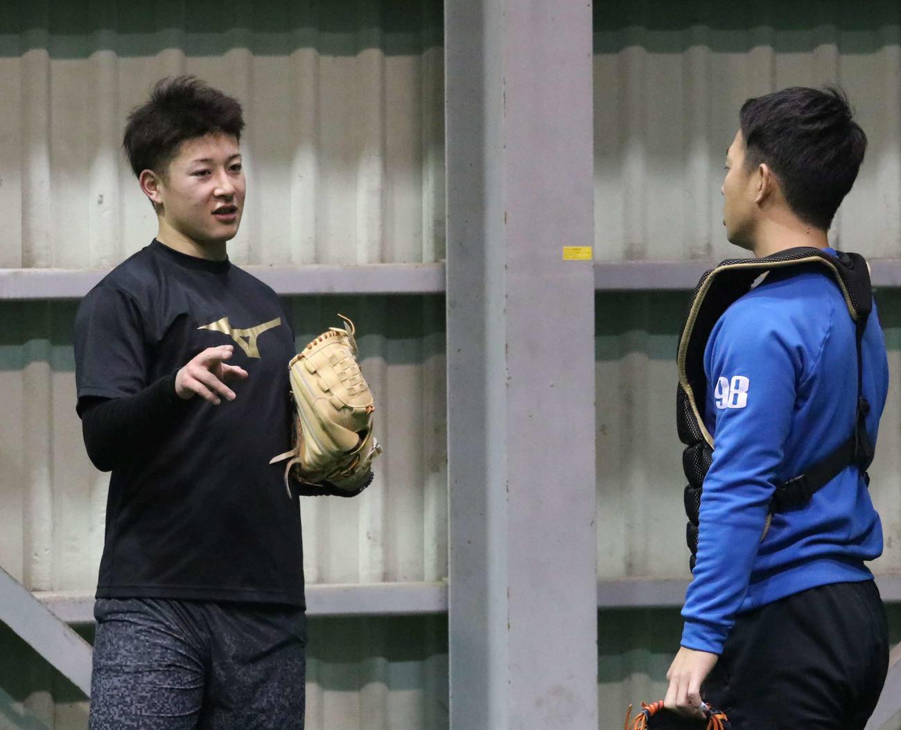 投球練習を終え、ブルペン捕手(右)と話す日本ハム吉田輝(撮影・山崎純一)