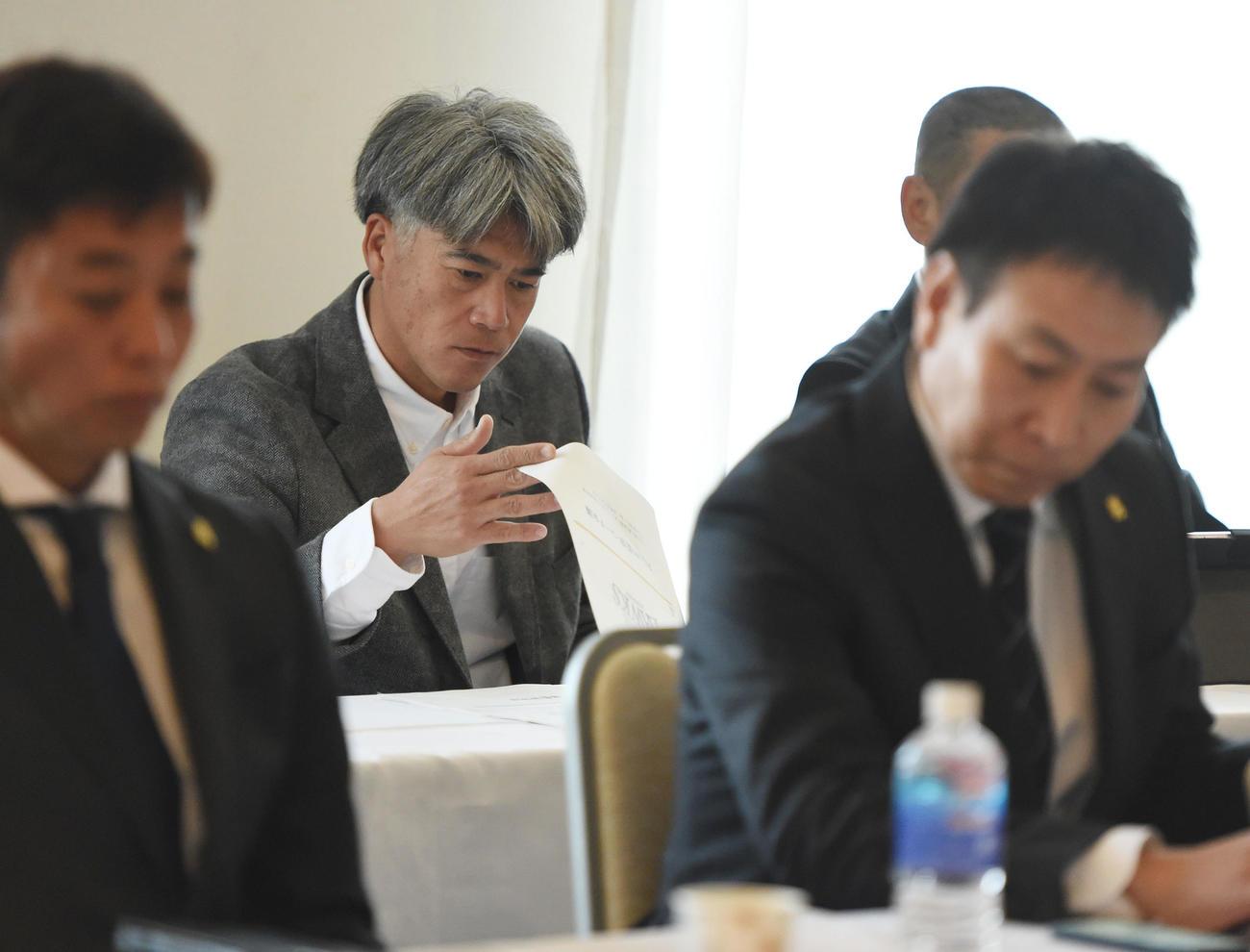監督、コーチ会議に出席し書類に目を通す会長付特別アドバイザーの城島(撮影・今浪浩三)