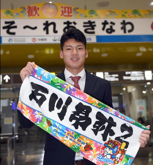 キャンプ地で売られる自身の記念グッズを手にする石川昂(2020年1月29日)