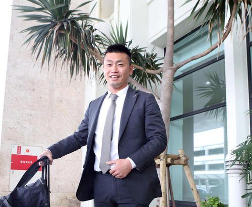 那覇空港に到着し、ヤシの木をバックに笑顔を見せる青木(2020年1月30日)
