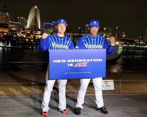 DeNA新主将に就任した佐野はラミレス監督とともに、今季のチームスローガンを掲げて横浜の夜景の前でガッツポーズ(撮影・鈴木正章)