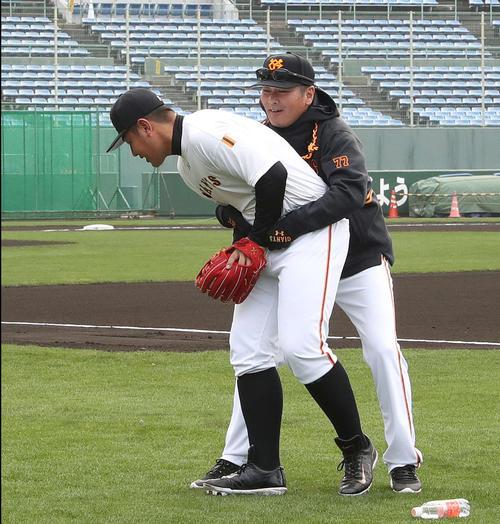 早出練習で巨人元木コーチ(右)とじゃれ合う岡本(撮影・河野匠)