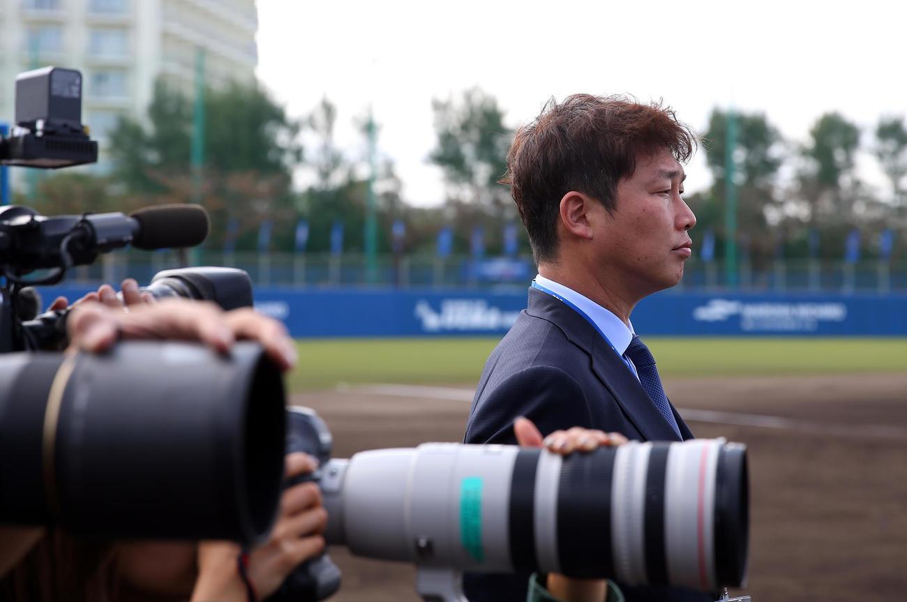 テレビの取材でDeNAキャンプに訪れた新井貴浩氏は真剣な表情で練習を見つめた(撮影・大野祥一)