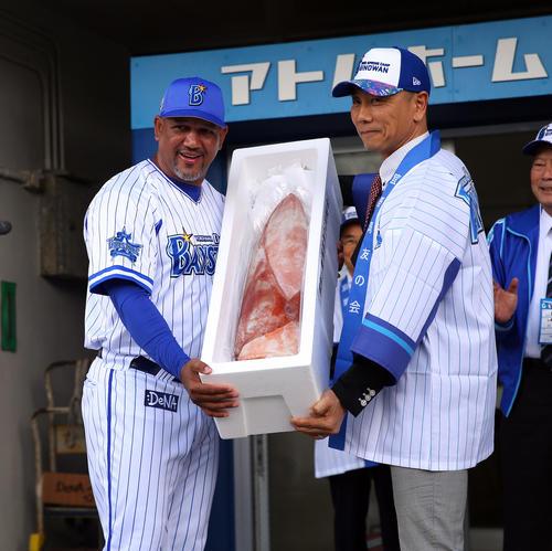 沖縄の名産品のソデイカを受け取るDeNAラミレス監督(左)(撮影・大野祥一)