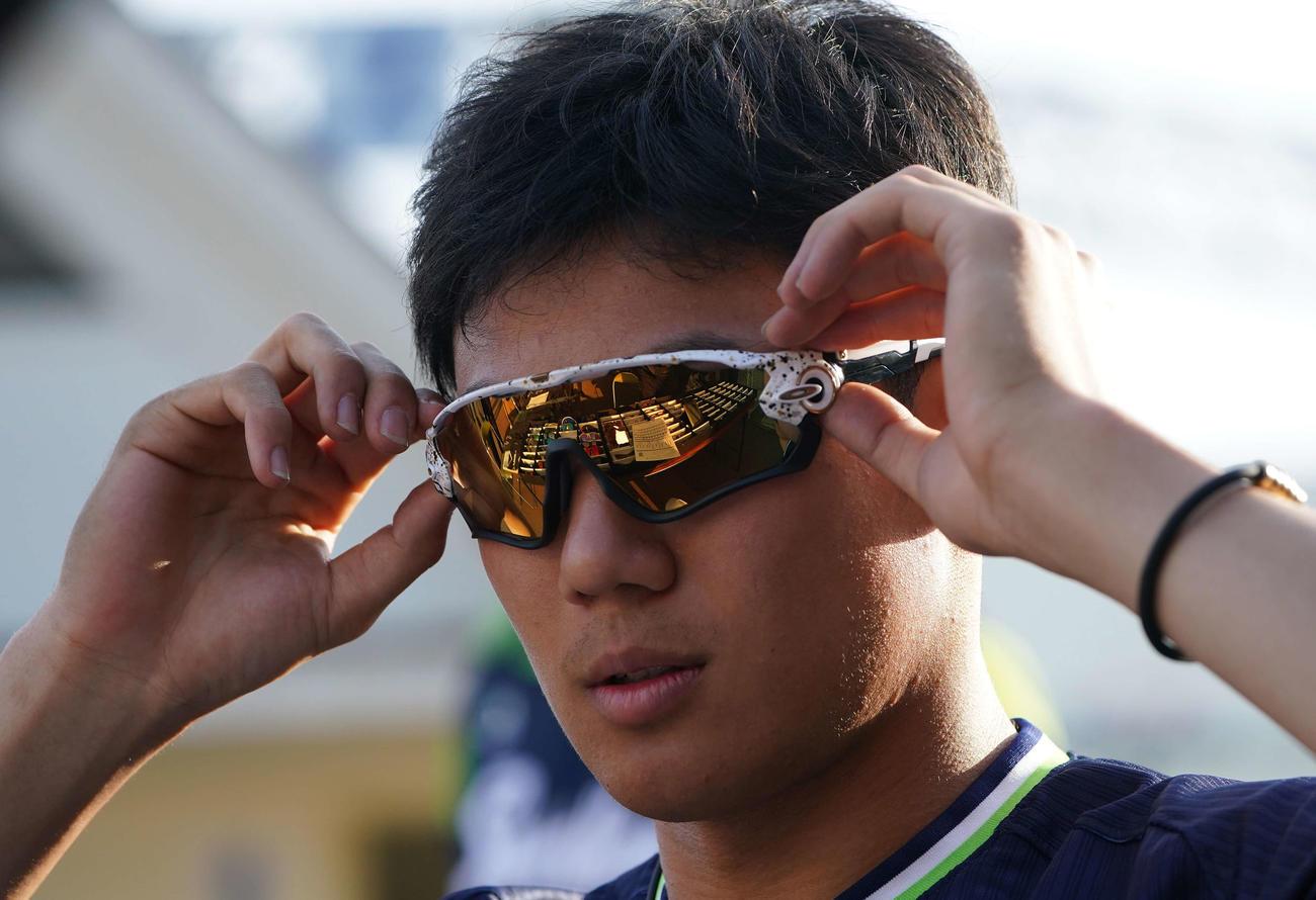 購入するサングラスを吟味するヤクルト奥川(撮影・鈴木みどり)