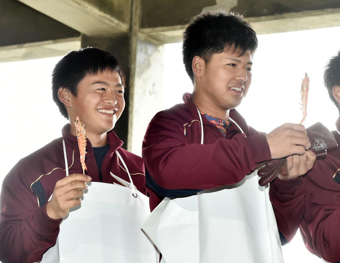休日に車エビの養殖場を訪れた楽天黒川(右)と水上は焼きたてのエビを手に笑顔を見せる(撮影・滝沢徹郎)