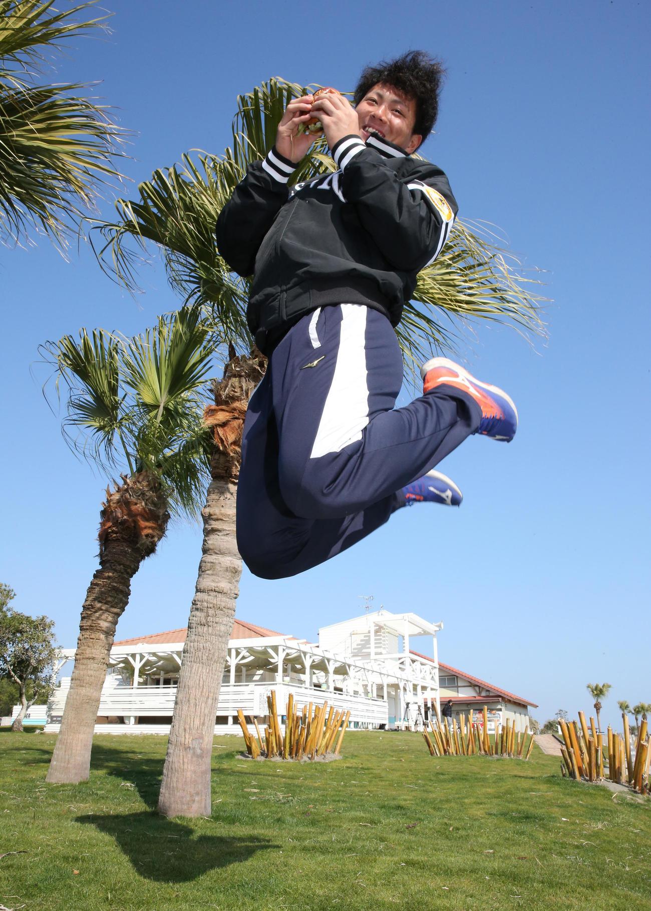 新人選手の1日体験で、手作りのハンバーガーを手にジャンプするソフトバンクドラフト1位の佐藤直樹(撮影・菊川光一)