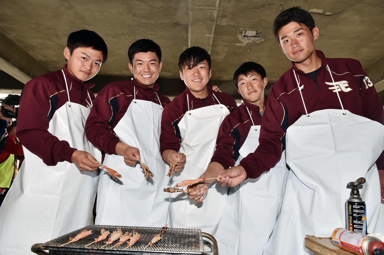 休日に車エビの養殖場を訪れた楽天新人選手は焼きたてのエビを手に記念撮影する。左から水上、津留崎、福森、小深田、小峯(撮影・滝沢徹郎)